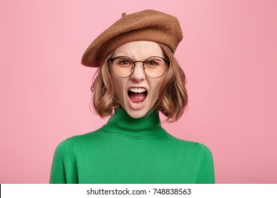 Furious irritated woman screams in despair, frowns face, being disturbed by something, quarrels with someone, confident in her rightness. Angry female teacher yells at naughty lazy noisy pupils