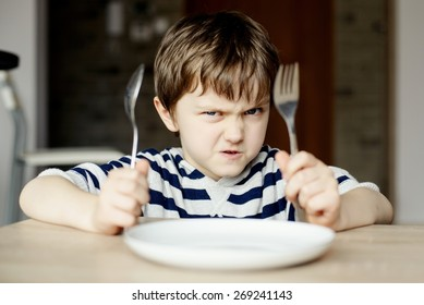 Furious little boy waiting for dinner. Holding a spoon and fork in the hand