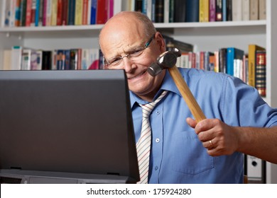 Furious man with bald patch hitting his computer with a hammer