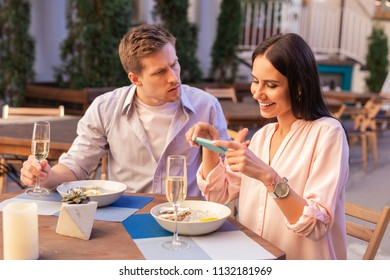 Furious man. Blonde-haired man feeling really furious sitting near blogger making photos of her food during date
