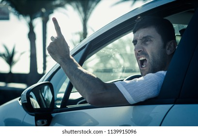 Furious man gesticulates with hand out of window while driving. Crazy driver yelling from car at sunrise. Stress, traffic rush hour, anxious, madness, rudeness concepts. Cold blue tone applied
