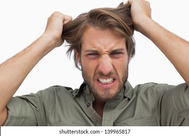 Furious man pulling his hair on white background