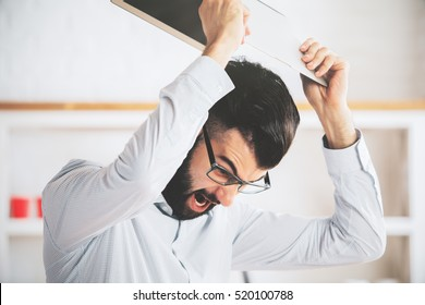 Furious man at workplace throwning his laptop. Anger issues and stress concept