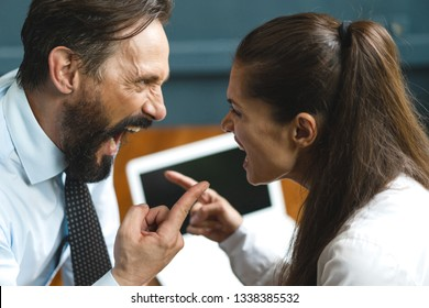 Furious Man Yells At Angry Woman. Loud Quarrel At Working Place. Angry Colleges Are Pointing Finger In A Rage And Screaming At Each Other. Portrait. Selective Shot. Unhealthy Working Environment