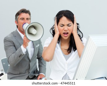 Furious manager shouting through a megaphone in a colleague's ears in the office