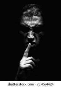 Furious mature man with an aggressive look making the silence sign in a violent and threatening way. Black and White, black background. Concept for threat, anger, rage, violence, danger, menace, fury