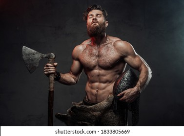 Furious medieval nord warrior with muscular build and naked torso posing in dark background holding his helmet and axe.