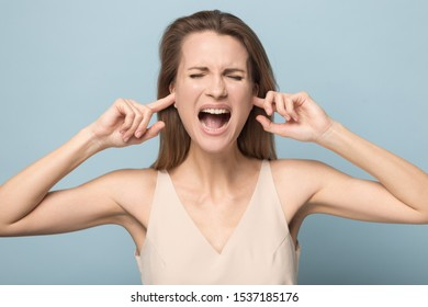 Furious millennial young woman isolated on blue studio background plug ears with fingers avoid loud disturbing noise, mad Caucasian female scream yell annoyed by noisy bothering sound