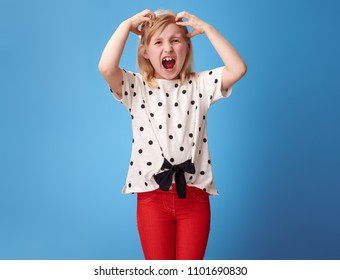 furious modern child in red pants scratching head isolated on blue background
