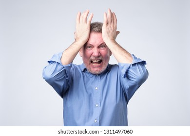 furious senior man holding his head in hands and screaming