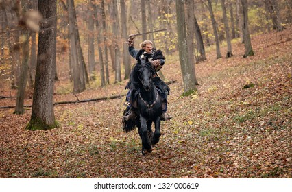 Furious Warrior Man riding a black horse. Reconstruction of a medieval war scene in the woods, in autumn