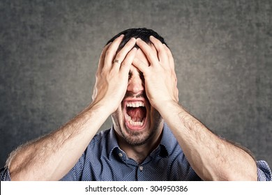 furious young men holding his head in hands and screaming
