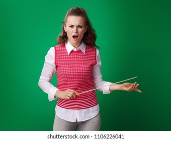 furious young student woman in a red waistcoat with a pointer on green background