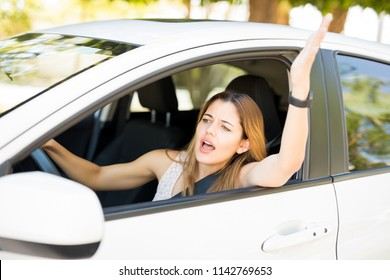 Furious young woman driver shouting and gesturing at other drivers during traffic on road