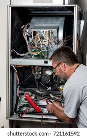 Furnace repair with a voltage meter used by a man