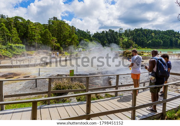 Furnas, Sao Miguel, Azores island, Portugal, August 14, 2020: Tourists watching the steam from Hot springs and fumaroles at the edge of lagoa das Furnas, volcanic calderas at Furnas Lake