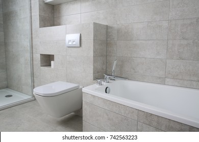 Furnished bathroom with white furniture, tiles in grey.