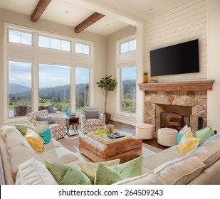 Furnished Living Room in Luxury Home on Sunny Day with Fireplace, TV, Large Bank of Windows, and Large Couch