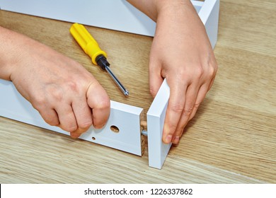 The furniture assembler joins together the two parts of the ready-to-assemble furniture with cam lock connections and wooden dowel pin, flat pack furniture assembly service, snap-together joints.