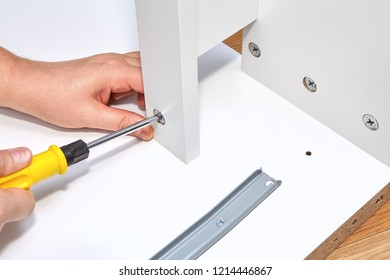 Furniture assembler tightens the cam lock nut with a screwdriver in the furniture made of particle board.