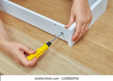 The furniture assembler tightens the screw into a wooden chipboard drawer using a screwdriver, ready-to-assemble furniture.