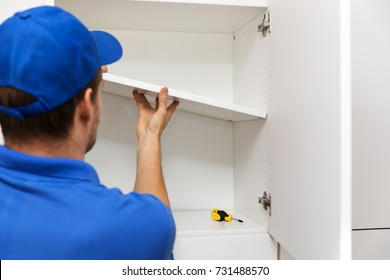 furniture assembly - worker installing cabinet shelf