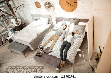 Furniture for bedroom. Interested couple examining quality of mattress for their future life together while lying in showroom