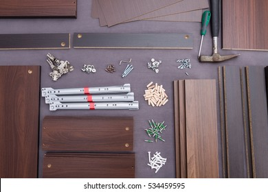 Furniture components and tools like a hammer and screwdriver flat lay on gray background of material.