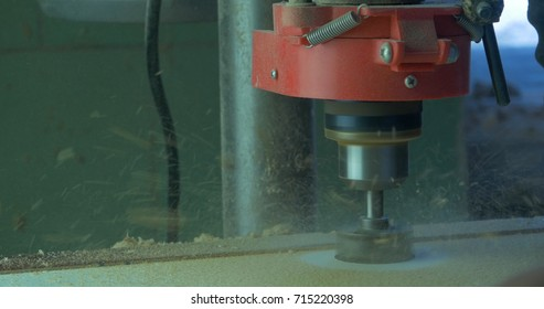 In a furniture factory, a man drills holes for furniture hinges. Drill Forstner. Forstner bit drilling into soft wood, closeup