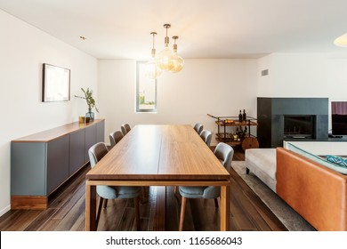 Furniture in living room interior. Dining table, mini bar with alcohol, fire place