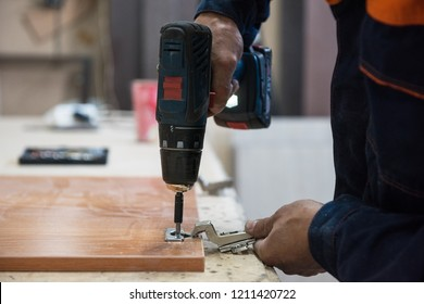 Furniture production concept: man working at machine and making furniture part