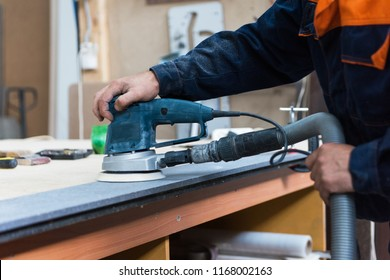 Furniture production or craft concept: worker polishing the stone surface of furniture part with polish machine
