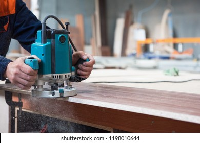 Furniture production or craft concept: worker polishing the wood surface of furniture part with polish machine