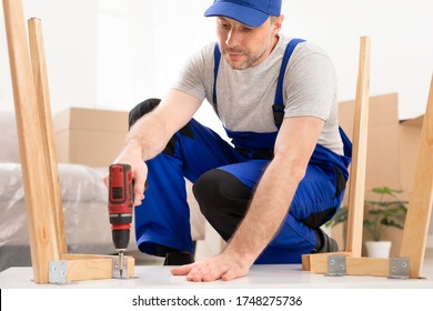Furniture Repair And Assembly. Workman Fixing Table Using Electric Drill Assembling And Furnishing Home After Renovation Indoor