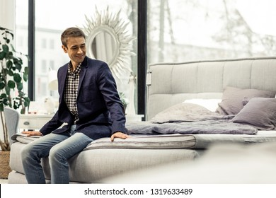 In furniture showroom. Handsome cheerful tricenarian gentlemen having comfort seat on new grey bed with fabric upholstery in stylish furniture showroom