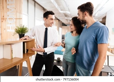 The furniture store manager demonstrates furniture to the buyers. A guy and a girl are listening with a good mood to the seller.