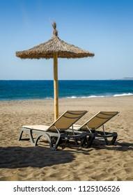 Furniture at Tejita beach and Atlantic ocean shore. Tenerife, Spain.