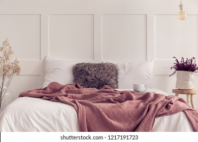 Furry pillow in the middle of king size bed with white bedding and dirty pink blanket, real photo with copy space on the empty wall