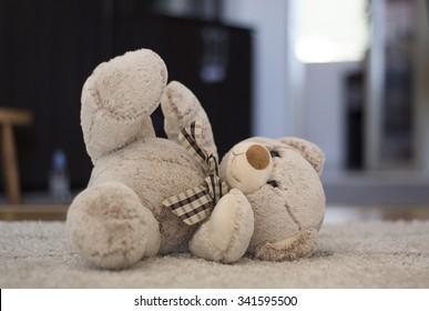 Furry teddy bear lying on the floor.