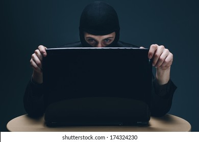 Furtive masked hacker accessing a laptop computer to steal data, plant malware or spy conceptual of cyber crime, online security and identity theft