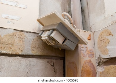 A fuse board hanging loose off the wall