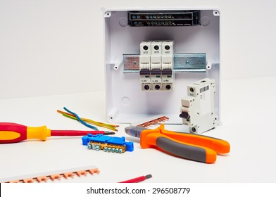 Fusebox with four automatic fuses during installation. Electricity distribution box. Electrical cabinet with tools.