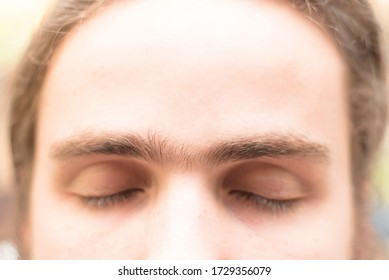 Fused eyebrows of a young man with unibrow of European appearance. The grooming on the face. Men's cosmetology. Soft focus.