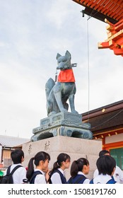 Fushimi Ward, Kyoto / Japan - 9/15/17: crowded street at fushimi inari taisha shrine, group of japanese kids on a field trip Fushimi inari, kitsune statue guarding the entrance to shrine, fox statue