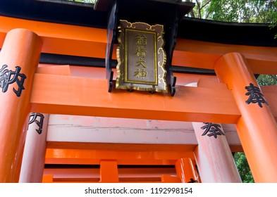Fushimi-Inari Taisha Shrine in Kyoto. Torii of the Shinto shrine. The kanji(Chinese character) of the pillar means dedication. The kanji(Chinese character) of a square board means Inari Taisha Shrine.