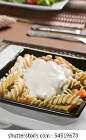 Fusilli colored with white sauce. Studio photogtraphy.