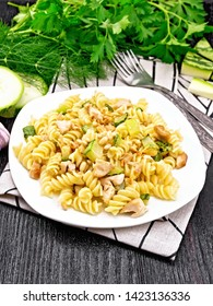 Fusilli pasta with chicken breast, zucchini, cream and pine nuts in a white plate on towel, garlic, fork and parsley on a dark wooden board background
