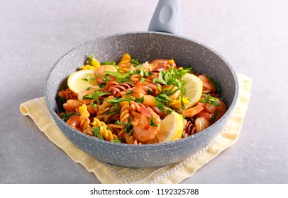 Fusilli pasta with lemony shrimps in a frying pan