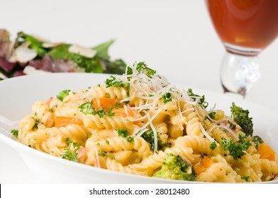Fusilli pasta with peppers, broccoli, and cheese sauce with side salad and tomato cocktail