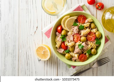 Fusilli pasta salad with tuna, tomatoes, olives and parsley on white wooden background. Top view. Copy space.
